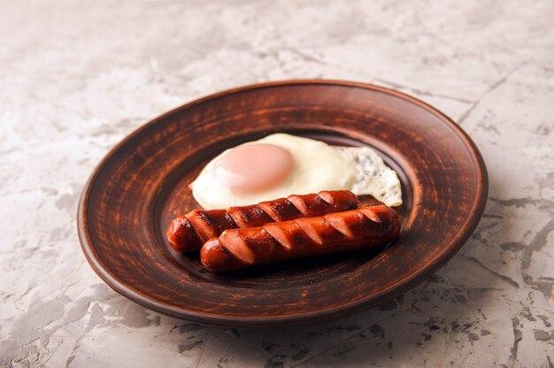 Жареные сосиски на тарелке с яичницей