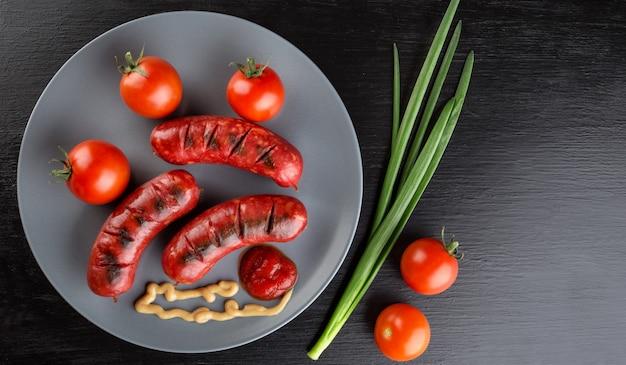 Жареные колбаски на тарелке с помидорами и кетчупом