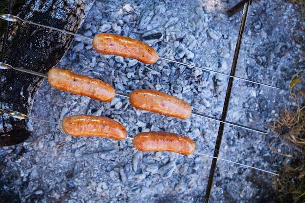 꼬치에 튀긴 소시지. 화재 근처의 여름 저녁, 좋은 주말. 클로즈업, 평면도.