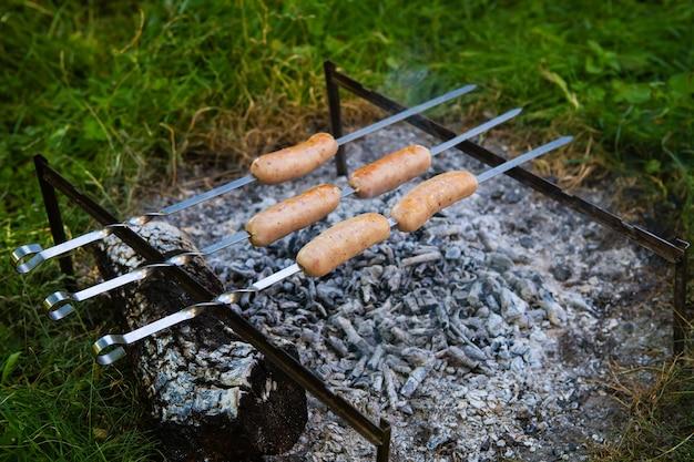 꼬치에 튀긴 소시지. 화재 근처의 여름 저녁, 좋은 주말.