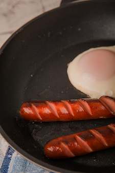 Fried sausages in a pan with scrambled eggs
