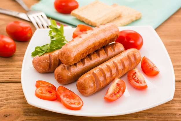 Fried sausages and tomatoes on a plate