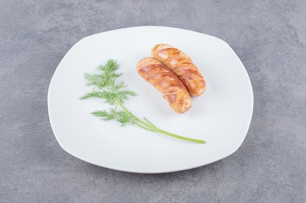 Salsicce fritte in un piatto bianco.