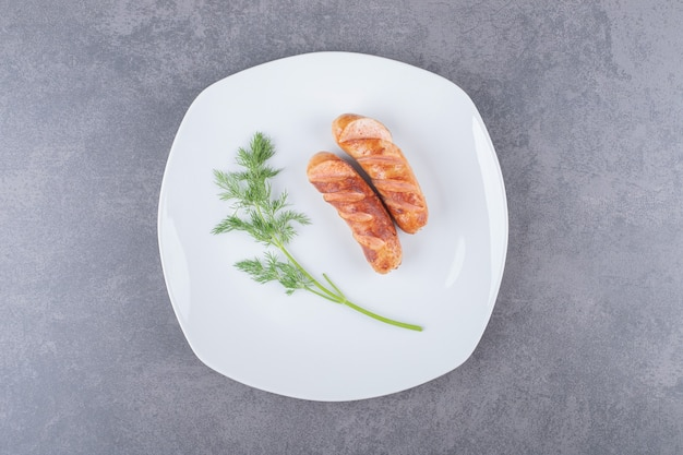 Salsicce fritte in un piatto bianco