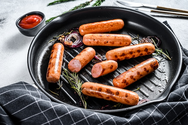 Fried sausages with garlic and herbs in a pan. black surface. top view