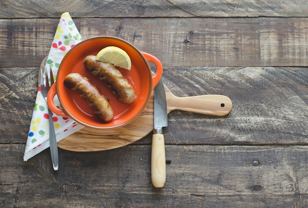 Fried sausages with a slice of lemon in a ceramic bowl