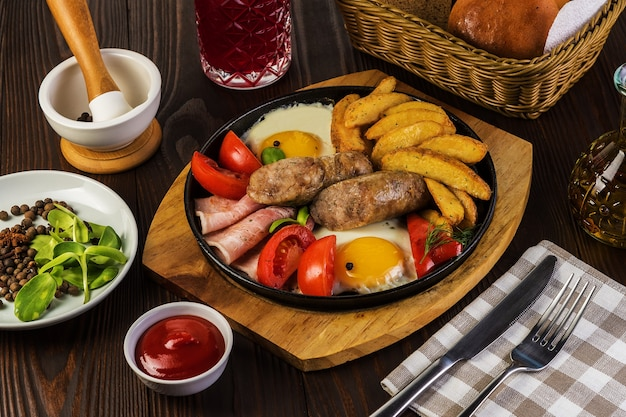 Fried sausages with with bacon and fried eggs and fried potatoes on a rustic background