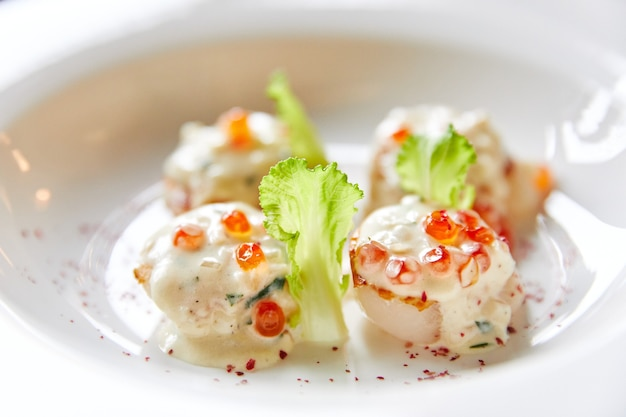 Жареные гребешки на тарелке, политые икорным соусом, украшенные салатом из морепродуктов