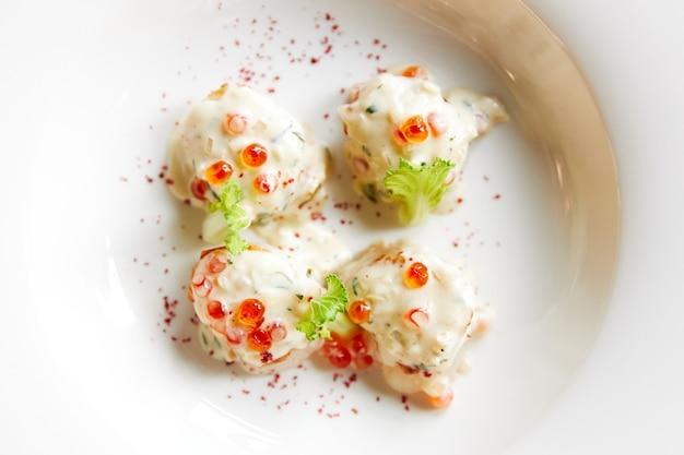 Жареные морские гребешки на белой тарелке, обсыпанные икорным соусом, украшенные салатом и специями, морепродукты