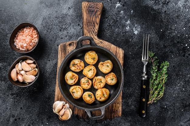 Жареные гребешки с масляным соусом на сковороде на деревянном столе. вид сверху.