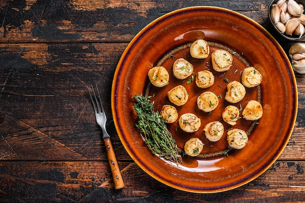 Жареные гребешки с масляным острым соусом в тарелке на деревянном столе. вид сверху.