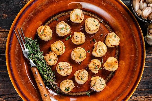 Жареные гребешки с масляным острым соусом в тарелке.