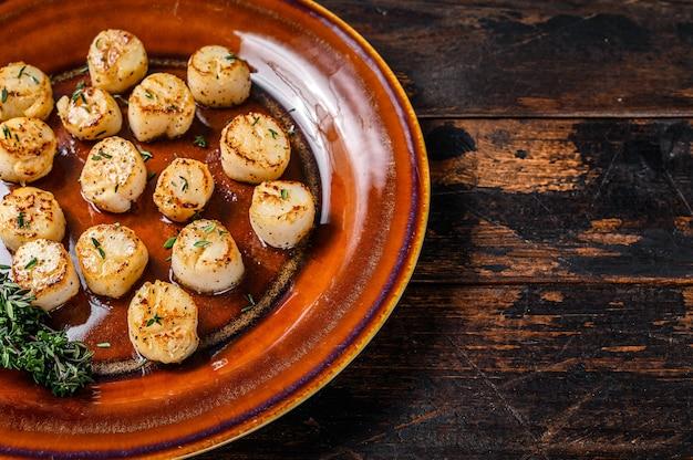 Жареные гребешки с масляным острым соусом в тарелке