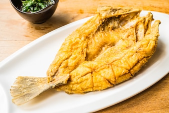Fried sea bass fish in white plate with spicy and sweet sauce