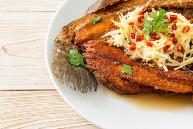 접시에 생선 소스와 매운 샐러드를 곁들인 튀긴 농어