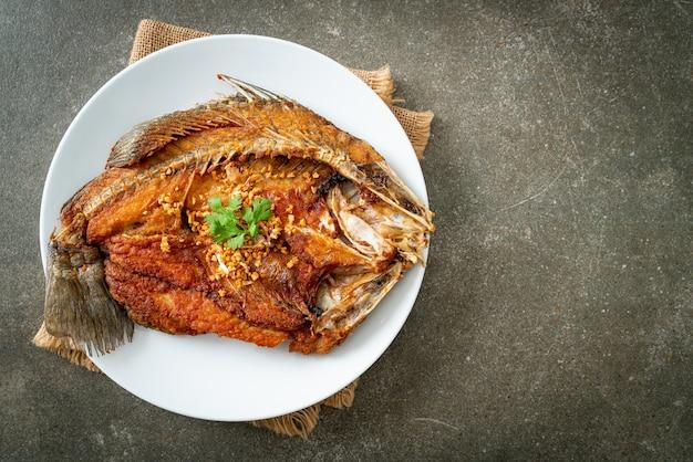 Жареный морской окунь с чесноком на тарелке