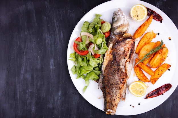 Fried sea bass with lemon, potatoes, salad and spices on a black wooden table