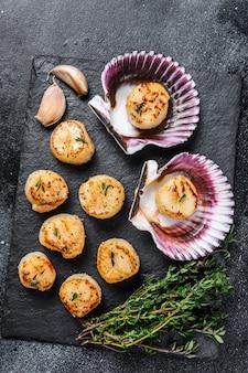 Жареное мясо гребешков из морепродуктов с маслом в раковинах на деревянном столе. вид сверху.