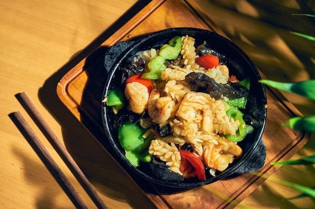 Жареные морепродукты (креветки, мидии, кальмары) в кисло-сладком соусе с сычуаньским перцем на сковороде. деревянный фон. китайская кухня