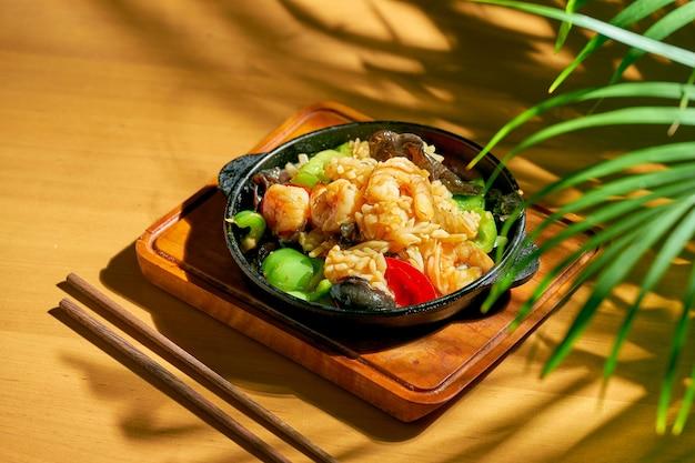 シーフード(エビ、ムール貝、イカ)を甘酸っぱいソースで揚げ、花椒をフライパンに入れます。木の背景。中華料理