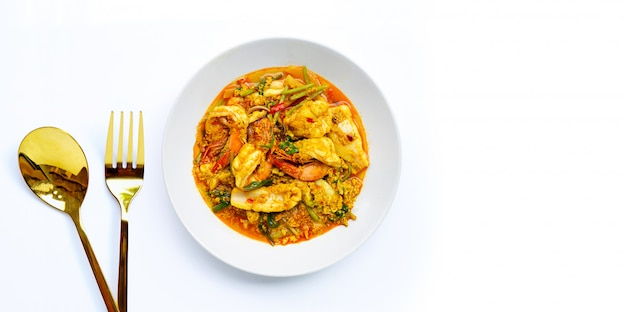 Fried seafood with curry powder on white surface