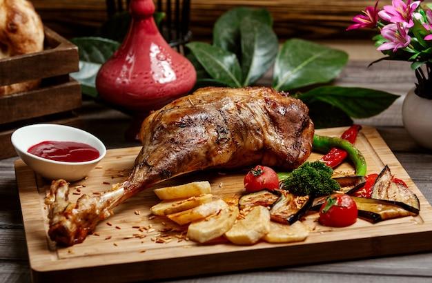 Fried sheep leg on wooden board