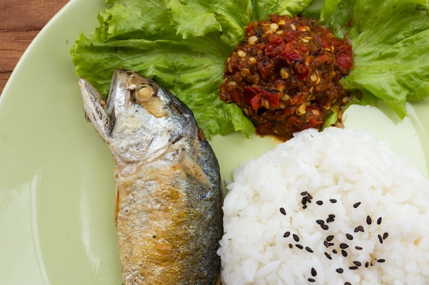 Fried short-bodied mackerel with rice on green plate.