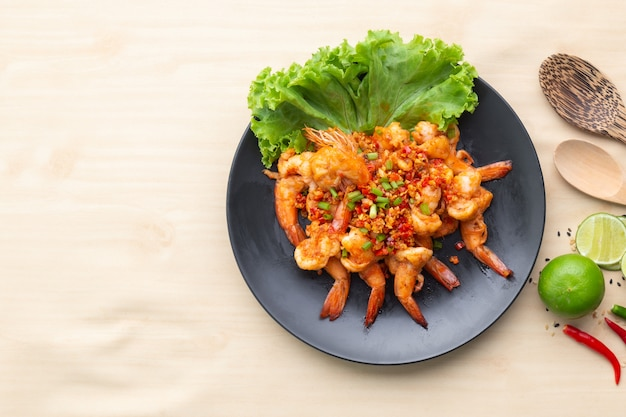 Fried shrimp with pepper and salt in black plate on wooden table, one of famous food in thailand.