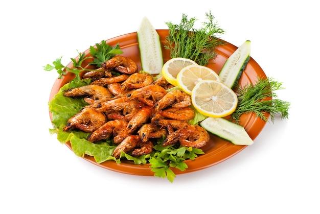 Жареные креветки, заправленные листьями салата, лимоном и огурцом. изолированные на белом фоне