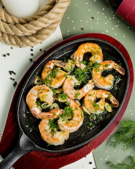 Fried shrimps in garlic and herbs sauce garnished with dill