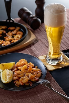 Fried shrimps and lemon in a black plate with glass of beer