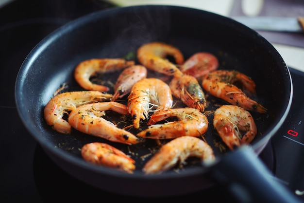 Fried shrimps in oil on pan with spices. closeup