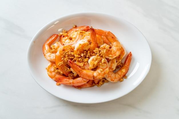 Жареные креветки или креветки с чесноком на белой тарелке - морепродукты