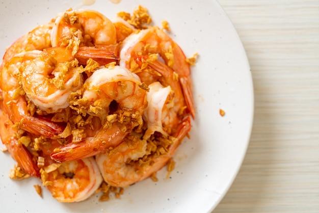 Жареные креветки или креветки с чесноком на белой тарелке. стиль морепродуктов