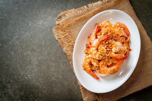 Жареные креветки или креветки с чесноком на белой тарелке