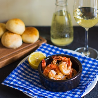 Fried shrimps in small ceramic pan served with lemon on blue checkered napkin