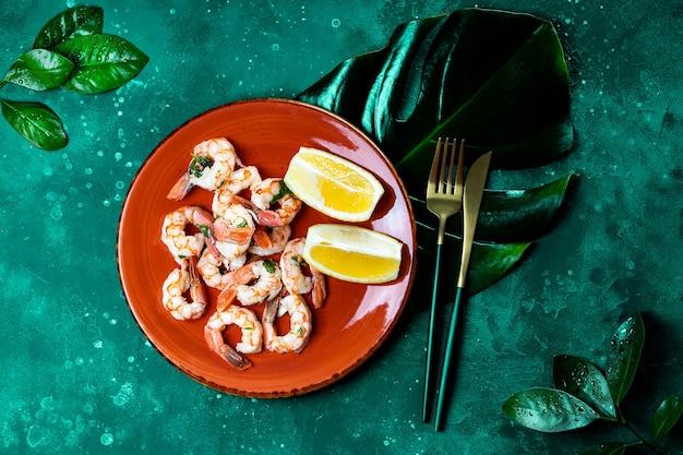Жареные креветки с лимоном на красной тарелке и зеленым листом монстеры, вид сверху. темно-зеленый фон