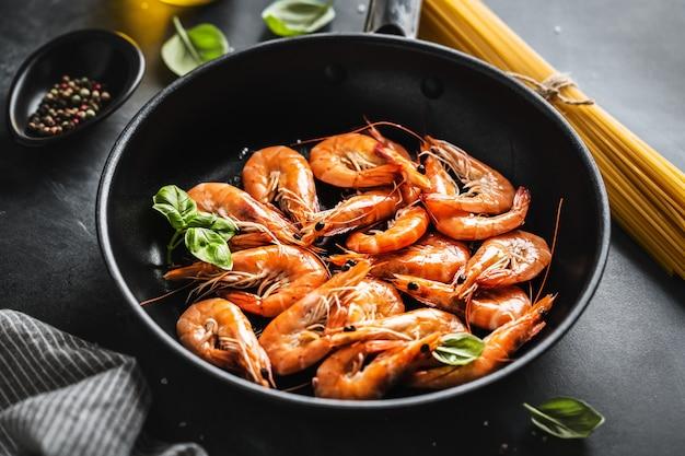 Жареные креветки с соусом на сковороде. крупный план.