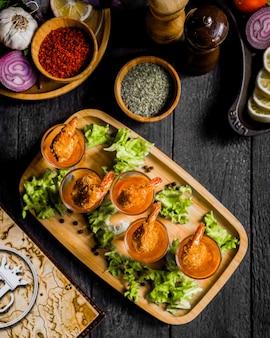 Жареные креветки с соусом на деревянной доске