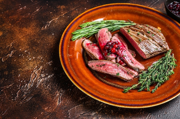 Fried sliced flank or bavette beef meat steak on a plate