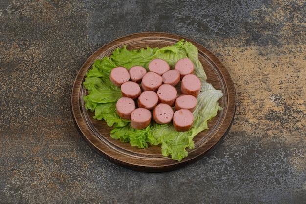 Жареные нарезанные сосиски на деревянной доске.