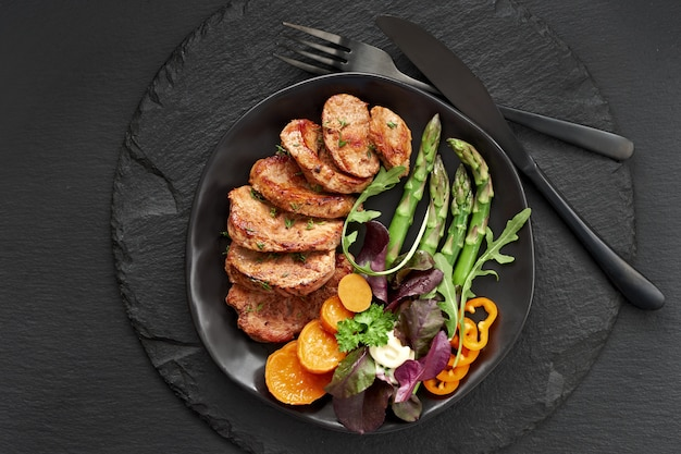 Fried slices of beef, sweet potato, asparagus and mixed green salad on black plate set for meal on dark slate