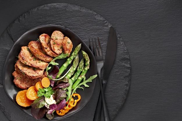 牛肉、サツマイモ、ブラックプレートにミックスサラダのスライスのスライス