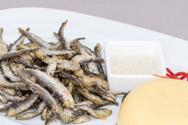 Fried small mackerel, with polenta and garlic sauce, decorated with herbs