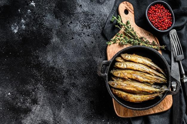トマトとコショウでテーブルの上の鍋で揚げたワカサギ。黒の背景。上面図。スペースをコピーします。