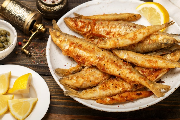 Fried smelt in a white plate, small fish, capers, lemon, pepper and salt on a wooden table, a delicious dinner in the rustic style
