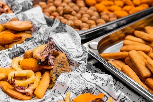 Жареные закуски в бумажных стаканчиках на городском рынке, быстрая уличная еда