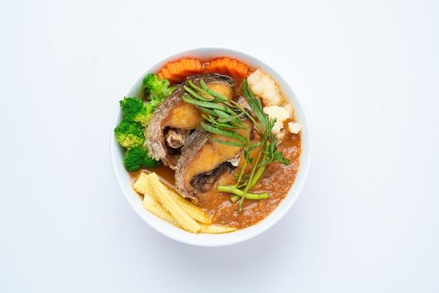 Жареная змееголов в кислом супе из пасты из тамаринда с овощным омлетом - азиатский или тайский кулинарный стиль изолированы