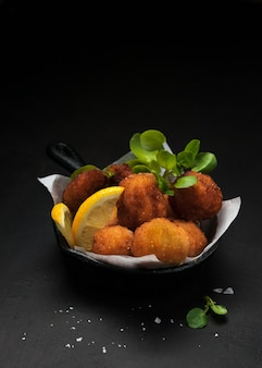 Fried spanish bacalao croquettes in iron pan made traditional tapas or snacks.
