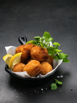 Fried spanish bacalao croquettes in iron pan made with breaded salted codfish.